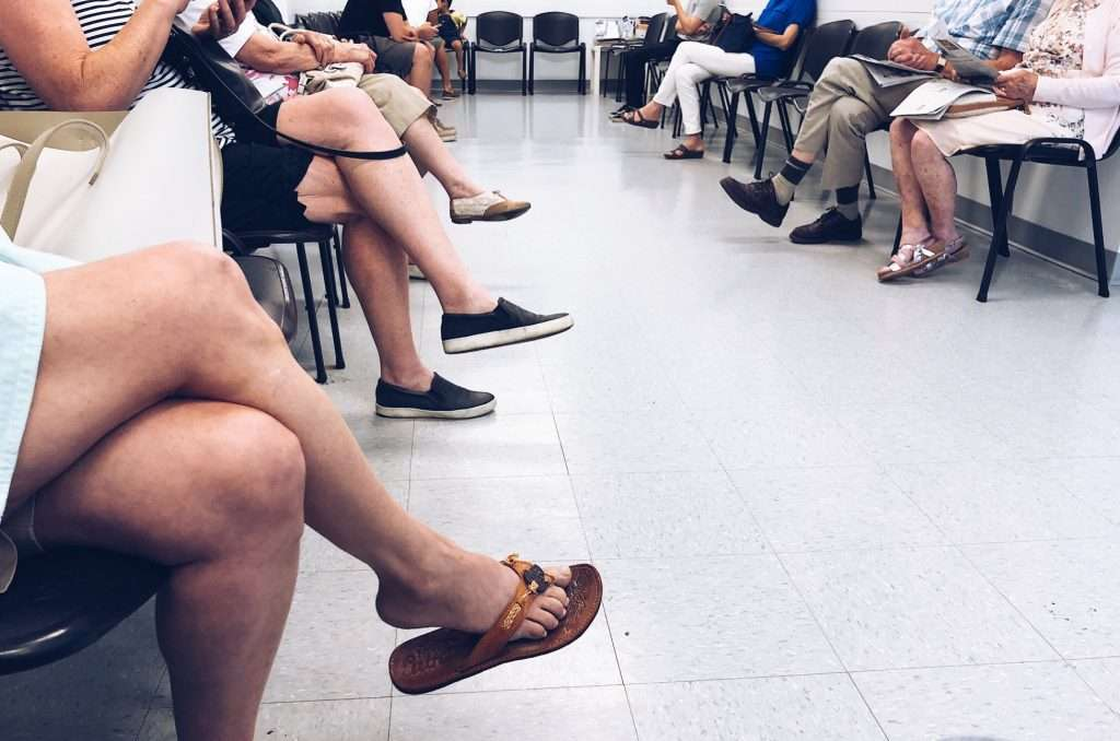 People sitting on chairs in a doctor office waiting room