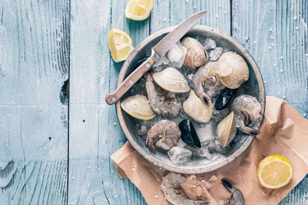 Bowl of clams on ice with lemons as an example of iron intake through seafood. Baseline diet is an important consideration before supplementing with iron IV therapy.